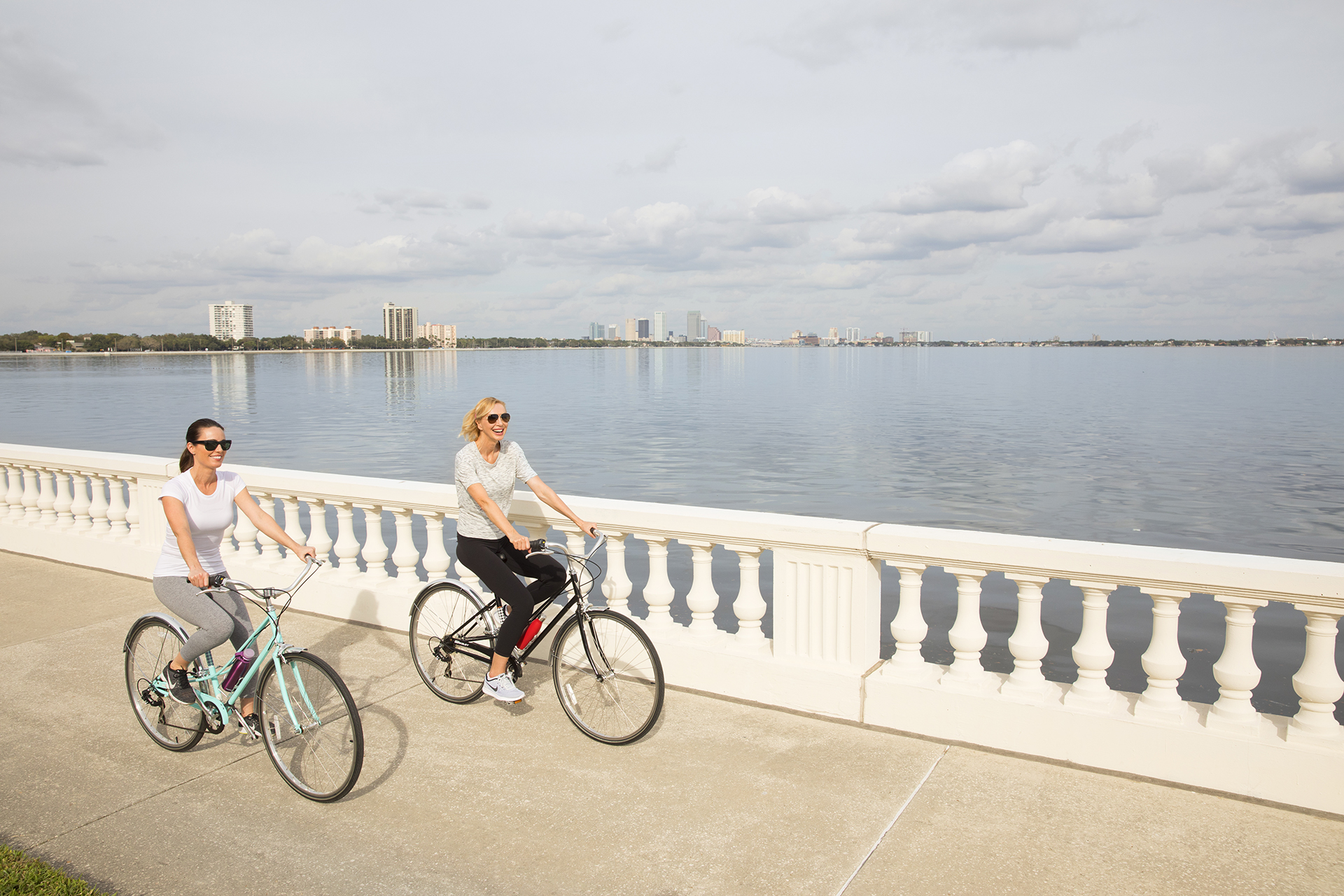 women riding bike on bayshore waterfront